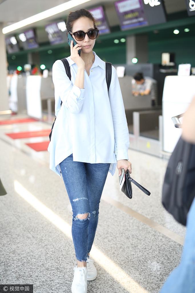 2017年7月2日讯,上海,张钧甯扎丸子头身穿破洞裤潮范现身上海机场