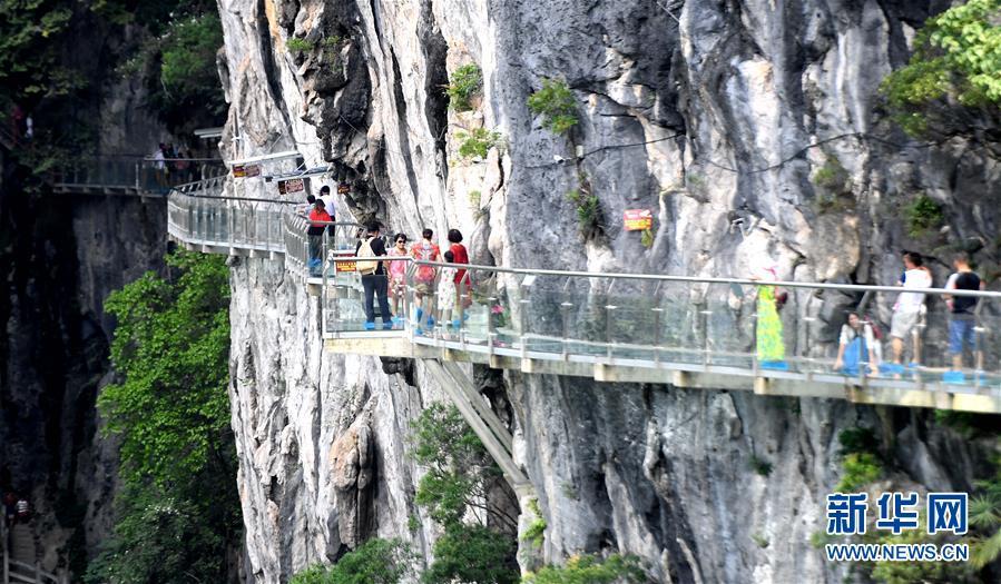 游客在融安县石门仙湖景区的玻璃栈道上游玩(8月1日摄).