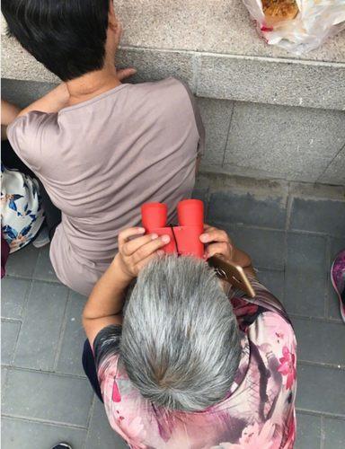 图为9月4日北京某幼儿园开学第一天,园外的家长们拿望眼镜暗中观察.