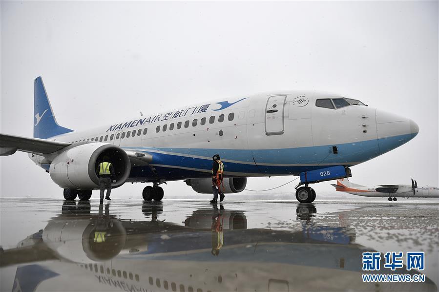1月4日,银川河东国际机场机务人员在除冰区对飞机进行检查.