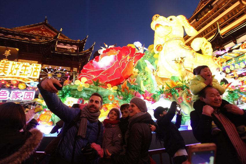 中外游客豫园赏灯,纷纷用相机和手机拍下美丽的灯会场景。