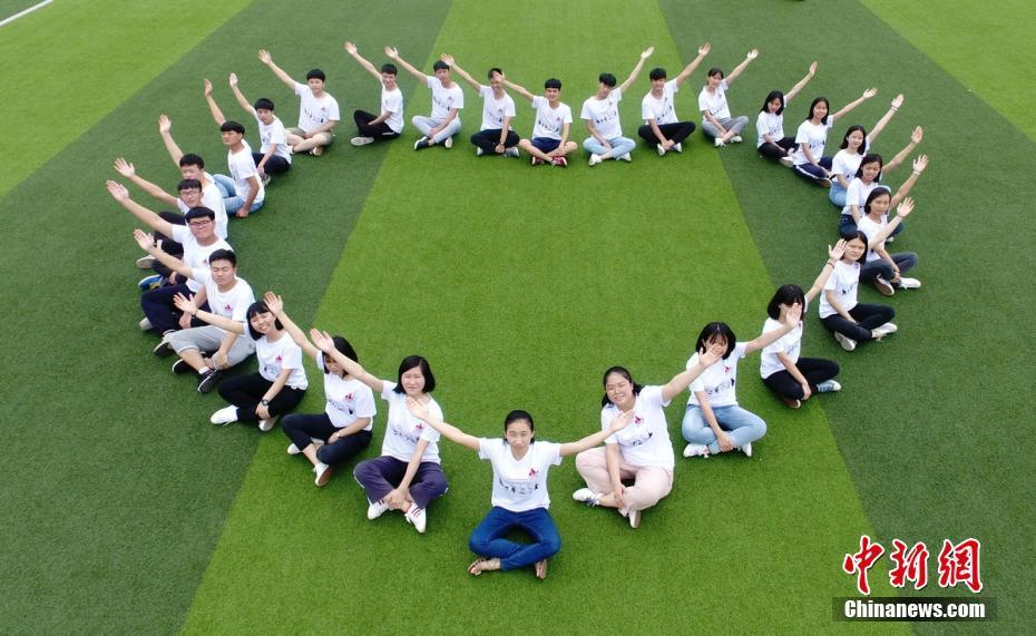 湖南道县第一中学高三年级学生在校园里摆出各种姿势拍摄创意毕业照图片