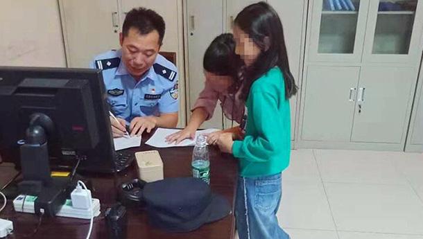 两小女孩国庆擅自出游-被接至派出所内民警陪写作业.jpg