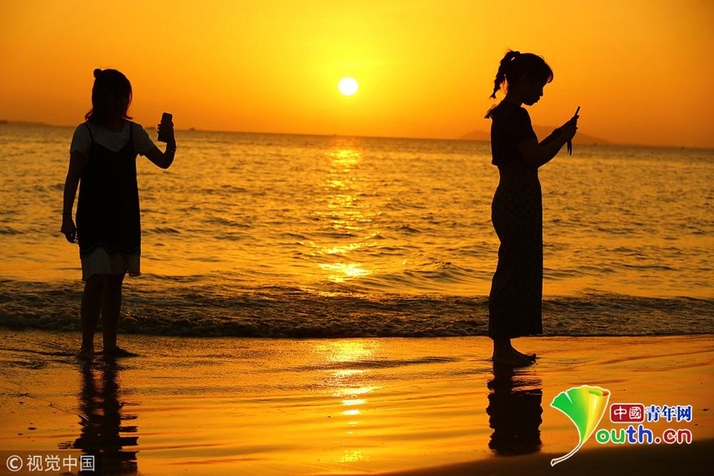 2018年12月19日,海南三亚,2名女孩在三亚湾海边夕阳中游玩.