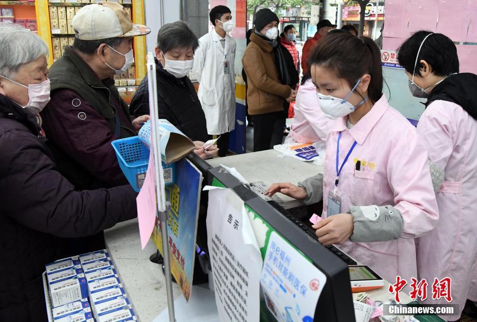 """战""""疫""""中的普通人:持续防控不懈怠    2月2日,福州市区一药店营业员佩戴口罩为市"""